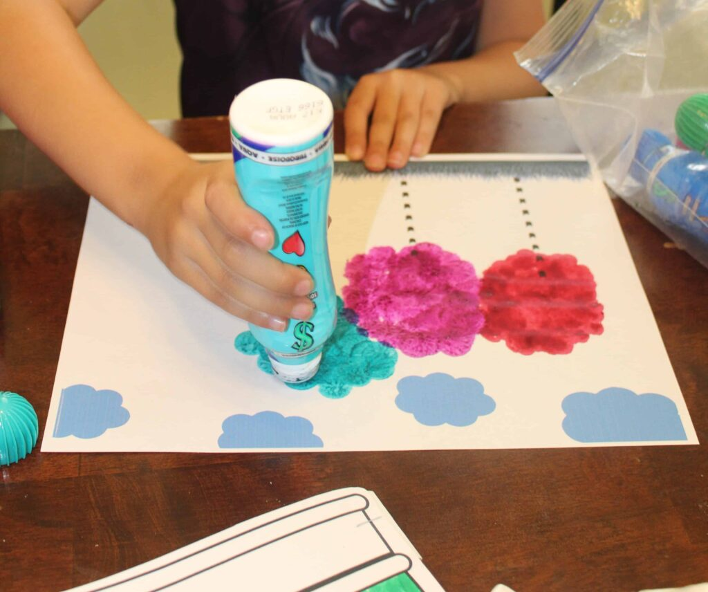 preschooler using do a dot markers to make truffula trees