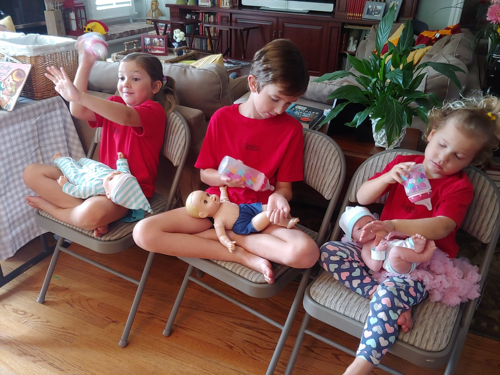 older siblings practicing with baby dolls