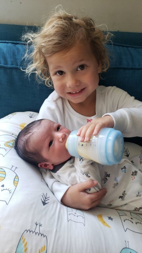 toddler feeding her baby brother