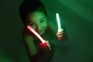 boy taking a glow stick bath