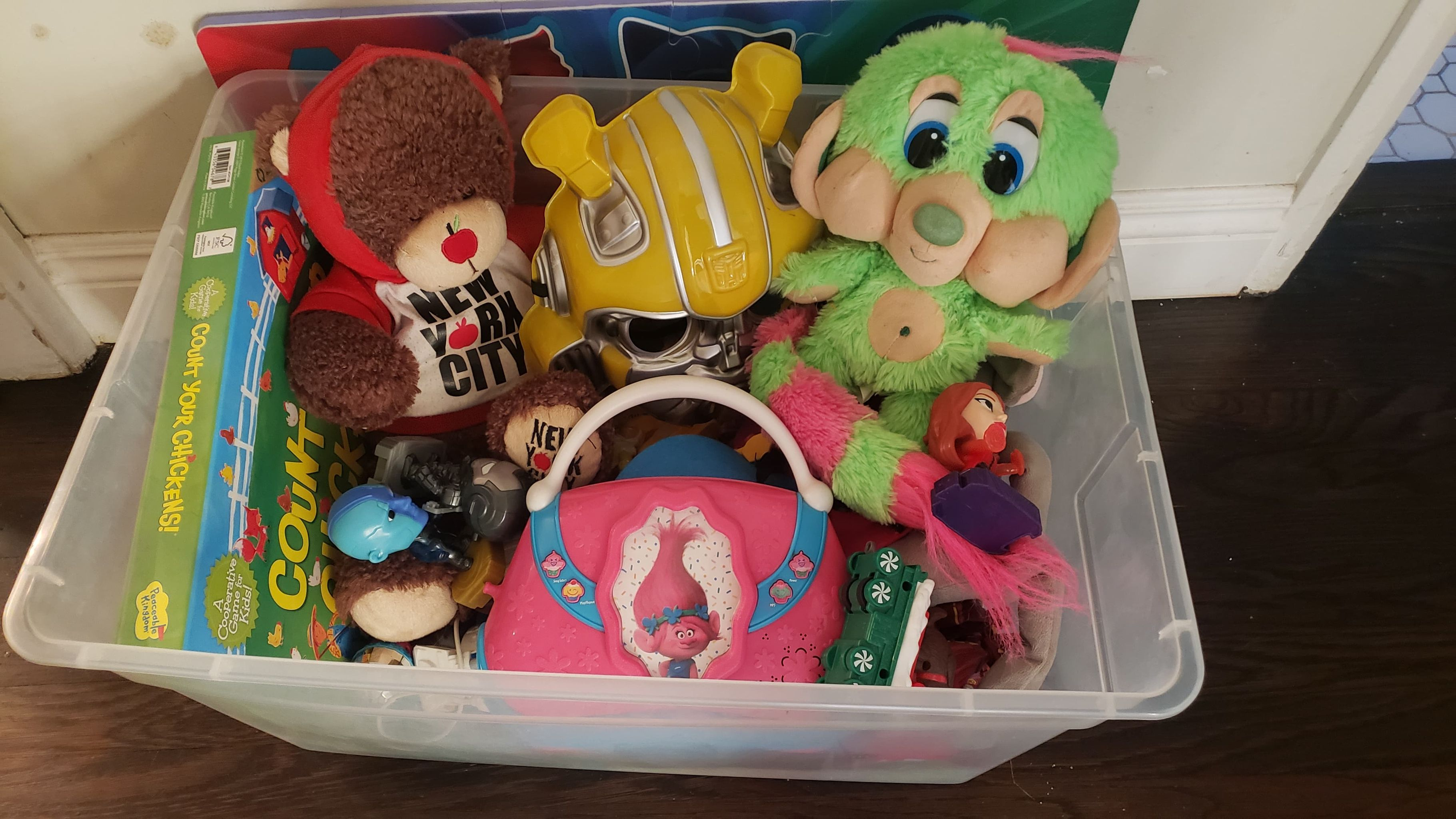 A plastic bin full of old toys to be given away.