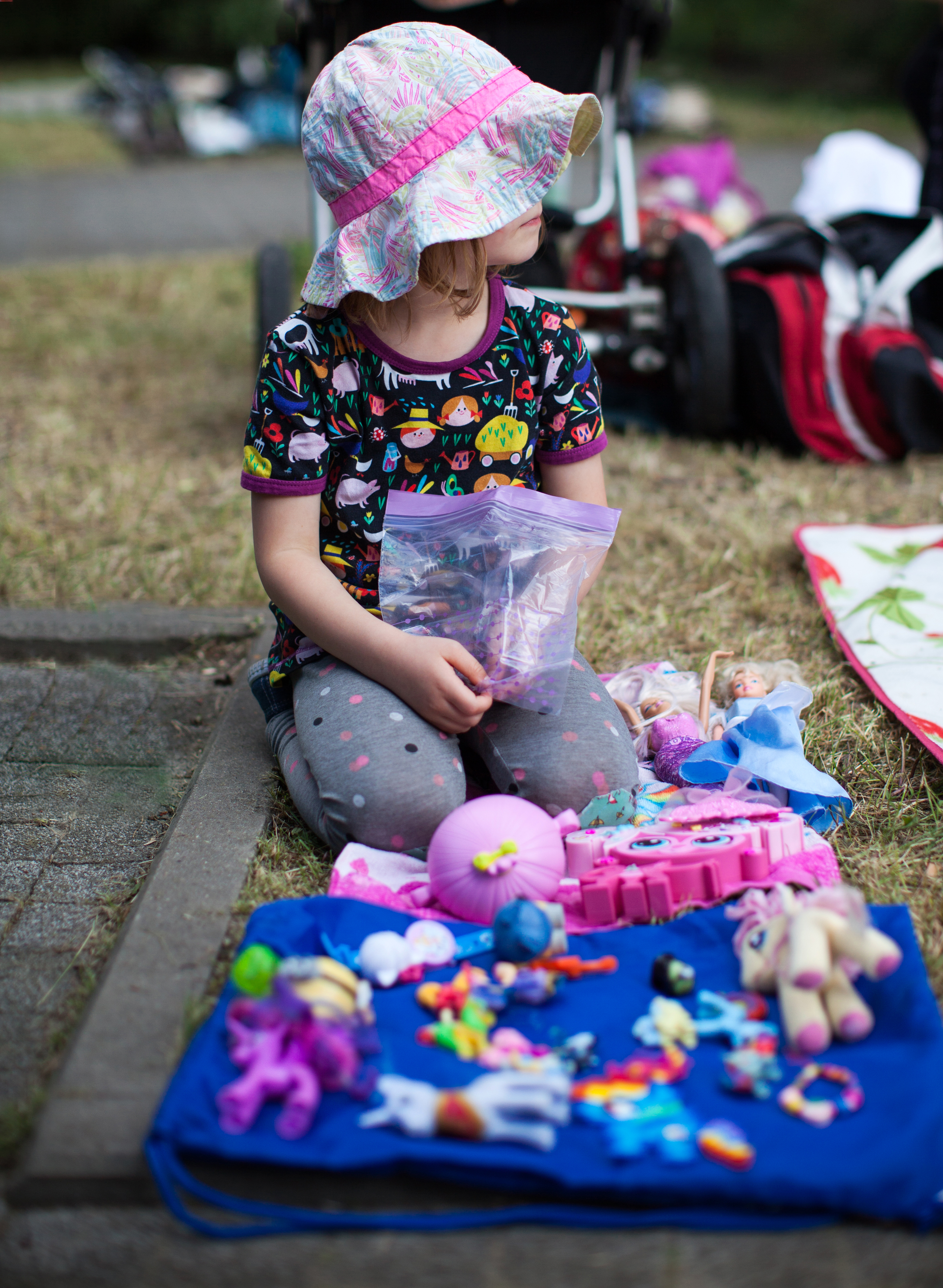 Child sitting in front of a blanket with toys arranged for a garage sale.