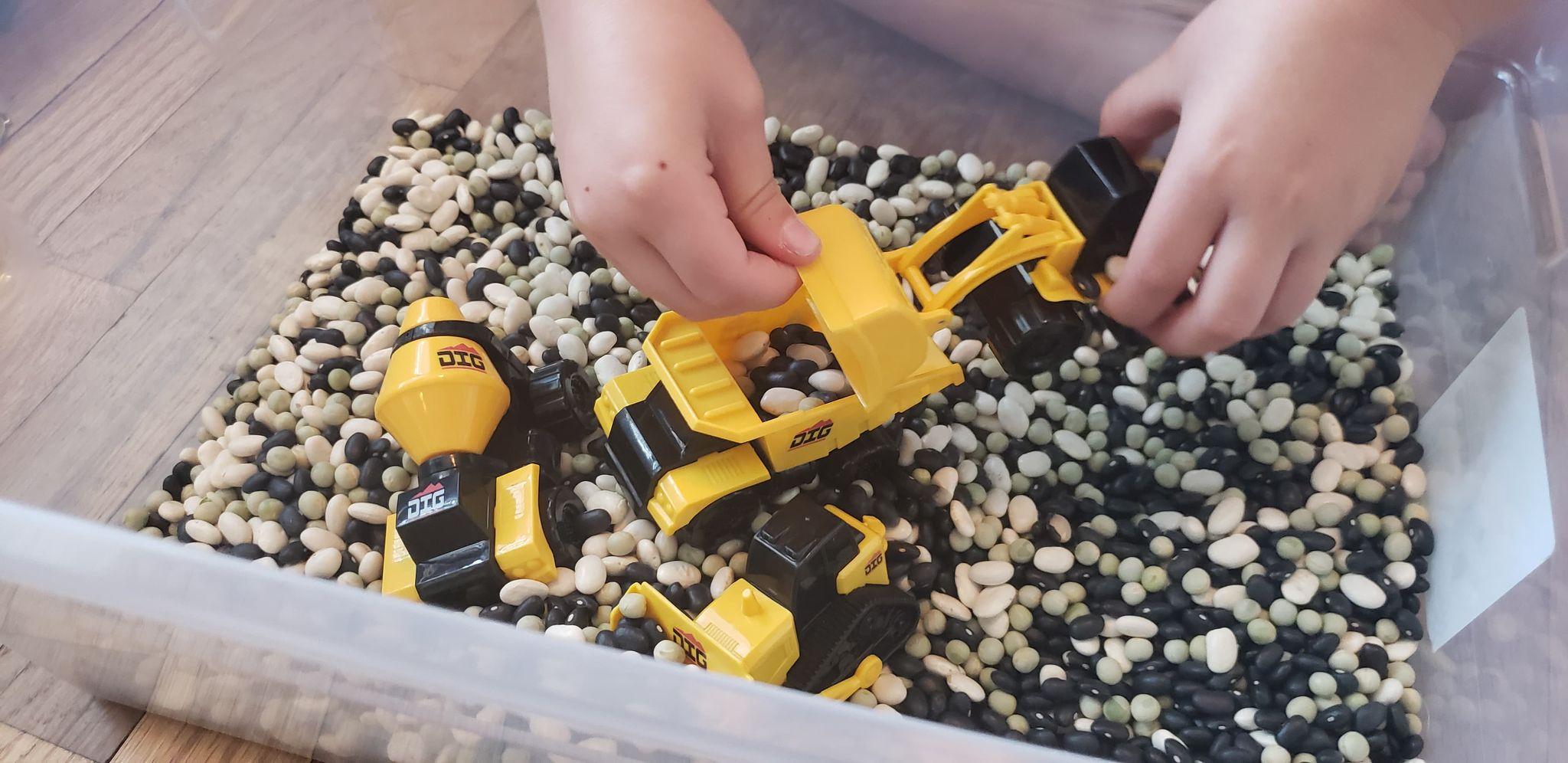 preschooler playing with construction sensory bin