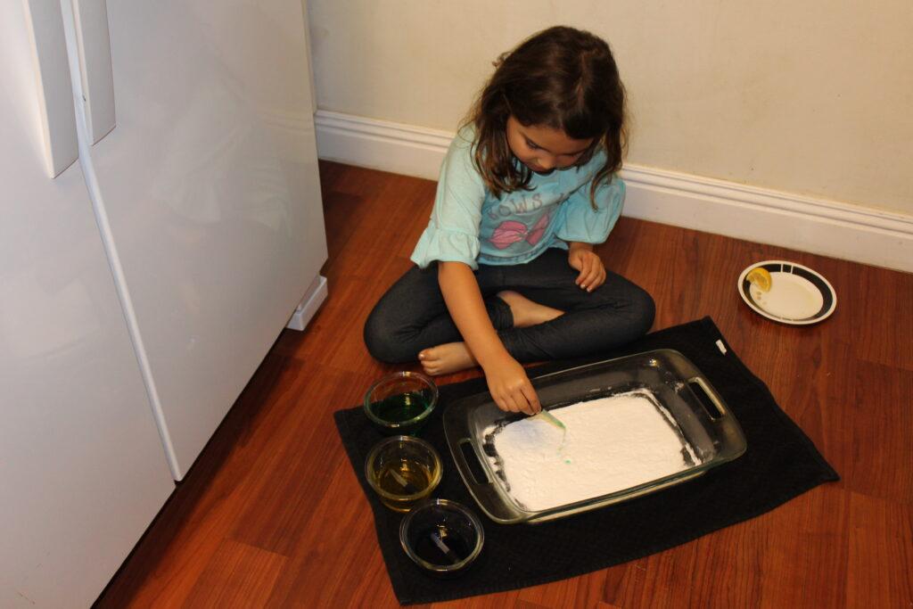 child experimetning with baking soda and vinegar