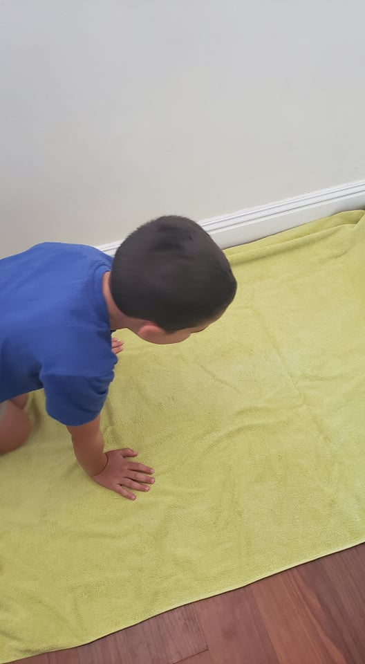 child setting up a towel for his sensory bin